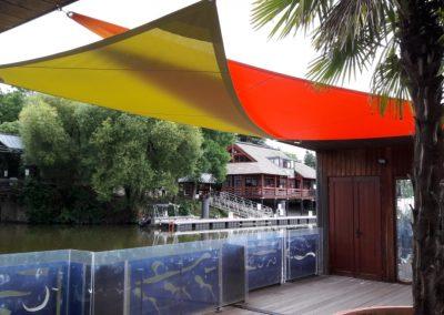 voiles d'ombrage sur une péniche orange et vert bambou à Nantes
